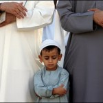 Little boy praying beside his Baba
