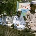 Muslim boys praying on a wall