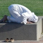 Man praying on a low wall