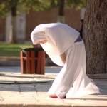 Muslimah praying alone on the sidewalk