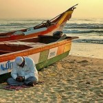 Man prays beside his fishing boat