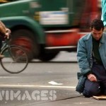 A man prays in the street beside his food truck