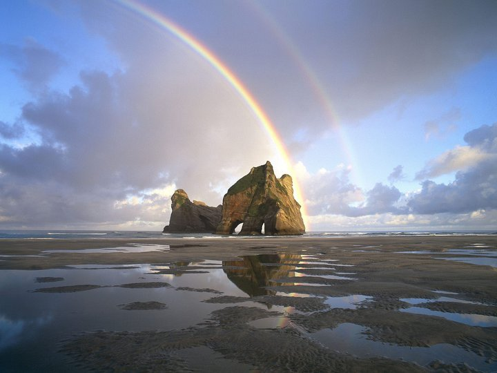 Rainbow over a beach rock