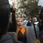 Woman raises fingers in a V for victory during protests in Egypt