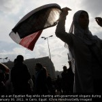 Woman holds up Egyptian flag during protests at Tahrir Square, Egypt