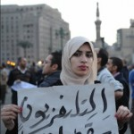 Solemn Egyptian woman holds up a protest sign in Tahrir Square