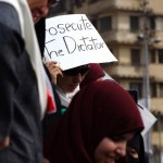 "Female protester holds sign saying, ""Prosecute the dictator"""