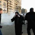 Egyptian woman covers her mouth as police shoot tear gas
