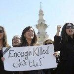 "Egyptian women carry a sign saying, ""Enough killed."""