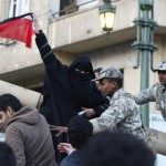 A veiled protester holds an Egyptian flag during demonstrations in Cairo