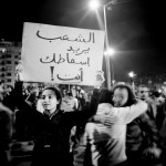 "A protester carrying a banner addressing Mubarak: ""The people want you to fall""..."