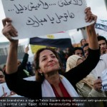 Woman brandishes a protest sign in Tahrir Square, Egypt