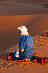 Touarag man praying in the Moroccan desert.