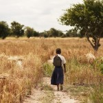 Tanzanian schoolgirl Sylvia walking through a field of scrub by her home to the road.