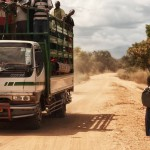 A truck passes Tanzanian schoolgirl Sylvia on a main road.