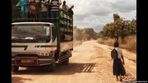 A truck passes Tanzanian schoolgirl Sylvia on a main road.