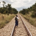 Tanzanian schoolgirl Sylvia walking along a railway,