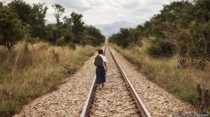 Tanzanian schoolgirl Sylvia walking along a railway,