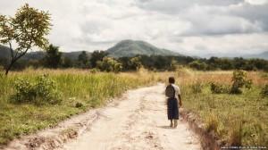 Tanzanian schoolgirl Sylvia on a path off a main road.