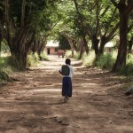Tanzanian schoolgirl Sylvia walking down a tree-lined avenue to her school.