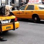 Cabbie prays on his cab during rush hour.