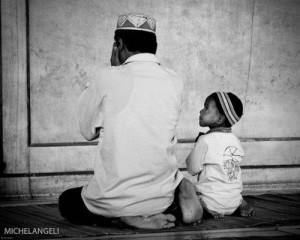 "Father and son praying, ""The immensity of this honor is mind-boggling if we really think about it in its reality. Reciting Quraan, the Words of Allah -- Speaking directly to Allah!"" - Shariffa Carlo"