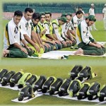 Pakistani cricket team prays on the field.