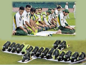 Pakistani cricket team prays on the field.