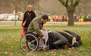 Man in a wheelchair prays at the park.