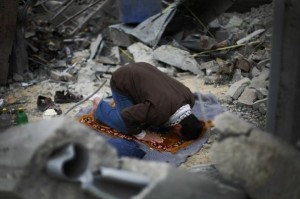 Muslim man prays in the rubble of his destroyed home.
