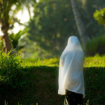 Indonesian woman prays beside a rice paddy.