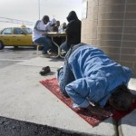 Muslim taxi driver prays beside a fast food outlet.