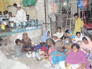 Poor families eating for free at the Hotel Gharib Nawaz